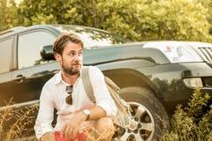 Uomo davanti all'automobile di SUV durante il viaggio di avventura di safari Fotografie Stock