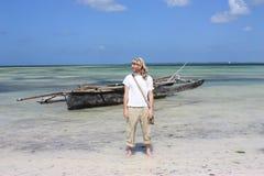 Uomo davanti alla barca africana sulla spiaggia Immagini Stock Libere da Diritti