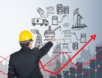 Uomo davanti alle icone di produzione di petrolio, effetto negativo dell'olio Immagine Stock