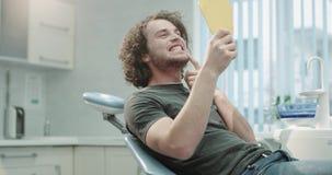 Uomo dei capelli ricci nella stanza dentaria della clinica che si siede sulla sedia del dentista che controlla il risultato di im stock footage