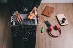 Uomo dei pantaloni a vita bassa che lavora con il computer portatile Fotografia Stock