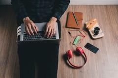 Uomo dei pantaloni a vita bassa che lavora con il computer portatile Fotografie Stock