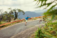 Uomo dei pantaloni a vita bassa che longboarding estremamente nei tropici Fotografie Stock Libere da Diritti