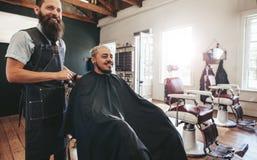 Uomo dei pantaloni a vita bassa che ottiene taglio di capelli al negozio di barbiere Fotografia Stock