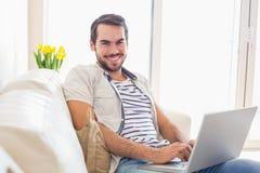 Uomo dei pantaloni a vita bassa che per mezzo del computer portatile sullo strato Immagine Stock