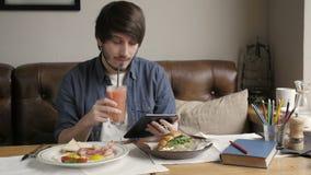 Uomo dei pantaloni a vita bassa che per mezzo della compressa di Digital che mangia prima colazione sana video d archivio