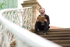 Uomo dei pantaloni a vita bassa che si siede sulle scale e sulla lettura Fotografie Stock