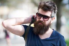 Uomo dei pantaloni a vita bassa con la barba alla moda e baffi che camminano nella città Ritratto del primo piano del giovane bel fotografia stock