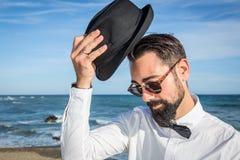 Uomo dei pantaloni a vita bassa con la barba e cappello sulla spiaggia Immagini Stock