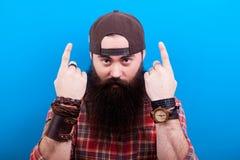 Uomo dei pantaloni a vita bassa con la barba lunga che indica su con entrambe le mani Fotografie Stock Libere da Diritti