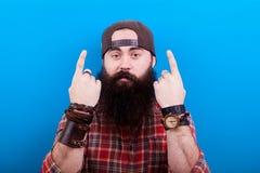 Uomo dei pantaloni a vita bassa con la barba lunga che indica su con entrambe le mani Immagini Stock