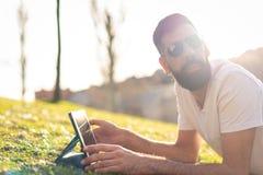 Uomo dei pantaloni a vita bassa facendo uso di una compressa digitale in un parco fotografie stock libere da diritti