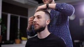 Uomo dei pantaloni a vita bassa nel negozio di barbiere e barbiere Barbiere che pettina fuori capelli Acconciatura quasi finita video d archivio