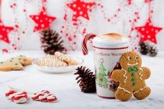 Uomo del biscotto del pan di zenzero e tazza calda di cappuccino Dessert tradizionale di Natale Copi lo spazio Immagini Stock