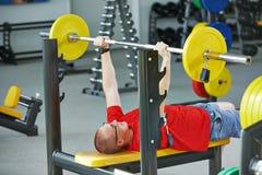 Uomo del Bodybuilder che fa le esercitazioni del muscolo con peso Fotografia Stock Libera da Diritti