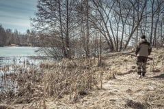 Uomo del cacciatore che cammina lungo la sponda del fiume durante la stagione di caccia della molla immagine stock libera da diritti