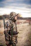 Uomo del cacciatore con il fucile da caccia in cammuffamento che sta nel campo rurale durante la caccia Fotografie Stock