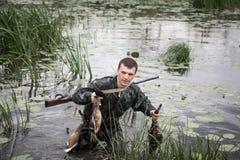 Uomo del cacciatore con la preda dopo una riuscita rottura di caccia attraverso regione paludosa immagini stock libere da diritti