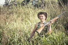 Uomo del cacciatore nel campo rurale con la rottura del fucile da caccia attraverso erba a lamella alta durante la stagione di ca Fotografia Stock Libera da Diritti
