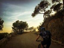 Uomo del ciclista che guida un mountain bike al tibidabo della montagna di tramonto nella città della Spagna di Barcellona fotografie stock