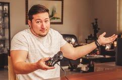 Uomo del Gamer che tiene un controllo con un ` accade espressione del ` Immagini Stock