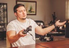 Uomo del Gamer che tiene un controllo con un'espressione indignata Immagine Stock