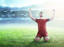 Uomo del giocatore di football americano celebrare il suo scopo con le armi e l'inginocchiamento alzati fotografie stock libere da diritti