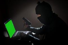 Uomo del ladro che incide computer e la pistola della tenuta Fotografia Stock Libera da Diritti