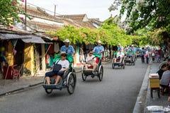 Uomo del locale e turistico del Vietnam che guida un ciclo tradizionale in Hoi Fotografie Stock Libere da Diritti