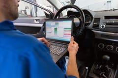 Uomo del meccanico con il computer portatile che fa sistema diagnostico dell'automobile fotografie stock libere da diritti