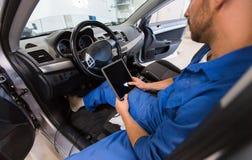 Uomo del meccanico con il pc della compressa che fa sistema diagnostico dell'automobile fotografia stock