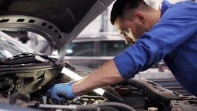 Uomo del meccanico con la chiave che ripara automobile all'officina 47