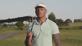 Uomo del Medio-Oriente concentrato giovani che distoglie lo sguardo con il club di golf sulla sua spalla Uomo bello che gioca gol video d archivio