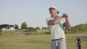 Uomo del Medio-Oriente concentrato giovani con il tatuaggio sulla spalla che gioca golf sul campo di golf L'uomo bello ha colpito video d archivio