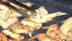 Uomo del movimento lento facendo uso delle tenaglie a girare le ali di pollo piccanti sul barbecue della griglia stock footage
