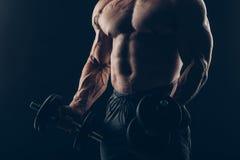 Uomo del muscolo che fa i riccioli del bicipite fotografie stock libere da diritti