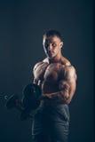 Uomo del muscolo che fa i riccioli del bicipite fotografie stock