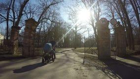 Uomo del padre con il retro portone del parco della passeggiata blu del passeggiatore in primavera 4K archivi video