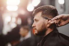 Uomo del parrucchiere nella sedia di barbiere immagine stock