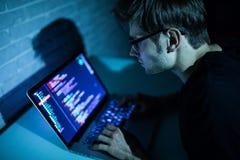 Uomo del pirata informatico che prova a violare sicurezza di Internet di ricerca del sistema informatico Fotografia Stock Libera da Diritti