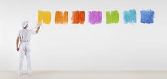Uomo del pittore con i campioni di colore della pittura del pennello isolati fotografia stock