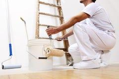 Uomo del pittore sul lavoro con un rullo, un secchio e una scala immagini stock libere da diritti