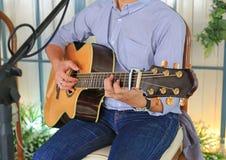 Uomo del primo piano che gioca chitarra acustica nel negozio del caffè fotografie stock