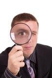 Uomo del primo piano che osserva tramite la lente d'ingrandimento Fotografia Stock Libera da Diritti