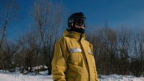 Uomo del primo piano nello sguardo scorrevole dello snowboarder del rivestimento giallo intorno nel parco della città di inverno video d archivio
