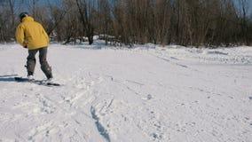 Uomo del primo piano in rivestimento giallo che fa scorrere su uno snowboard nel parco della città archivi video