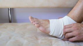 Uomo del pronto soccorso che applica fasciatura per il piede danneggiato e la caviglia che si siedono sullo strato a casa video d archivio