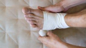 Uomo del pronto soccorso che applica fasciatura per il piede danneggiato e la caviglia che si siedono sullo strato a casa stock footage