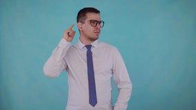 Uomo del ritratto con indebolimento dell'udito con una protesi acustica su un fondo blu video d archivio