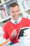 Uomo del ritratto in occhiali della tenuta delle biblioteche Immagini Stock Libere da Diritti